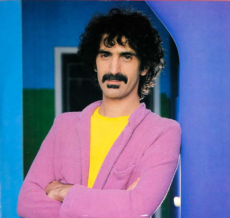 Large full-page photo of Frank Zappa wearing a pink jacket and yellow sweater