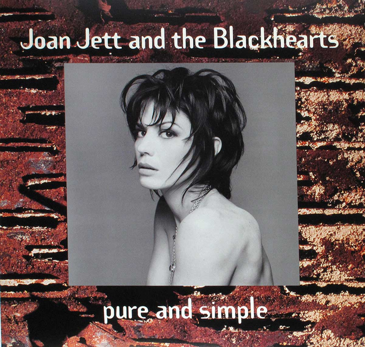 The photo shows a black and white nude Joan Jett portrait photo on a brick wall background