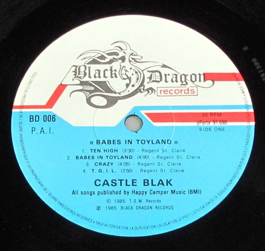 "Close up of Side One record's label ""Babes In Toyland by Castle Black"" White and Blue Colour Black Dragon Records Record Label Details: BD 006 © 1985 T.O.M. Records Copyright ℗ Black Dragon Records Sound Copyright"
